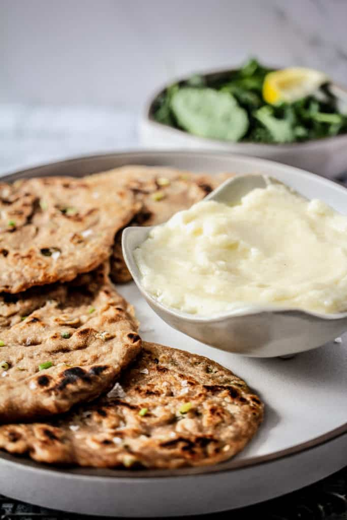 bowl garlic sauce with a plate of scallion pancakes