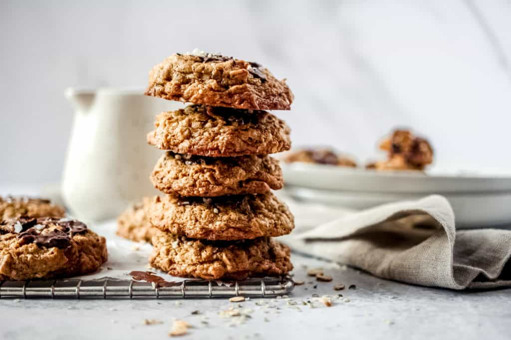 stacked oatmeal chocolate chip cookies on a cooling rack with a linen