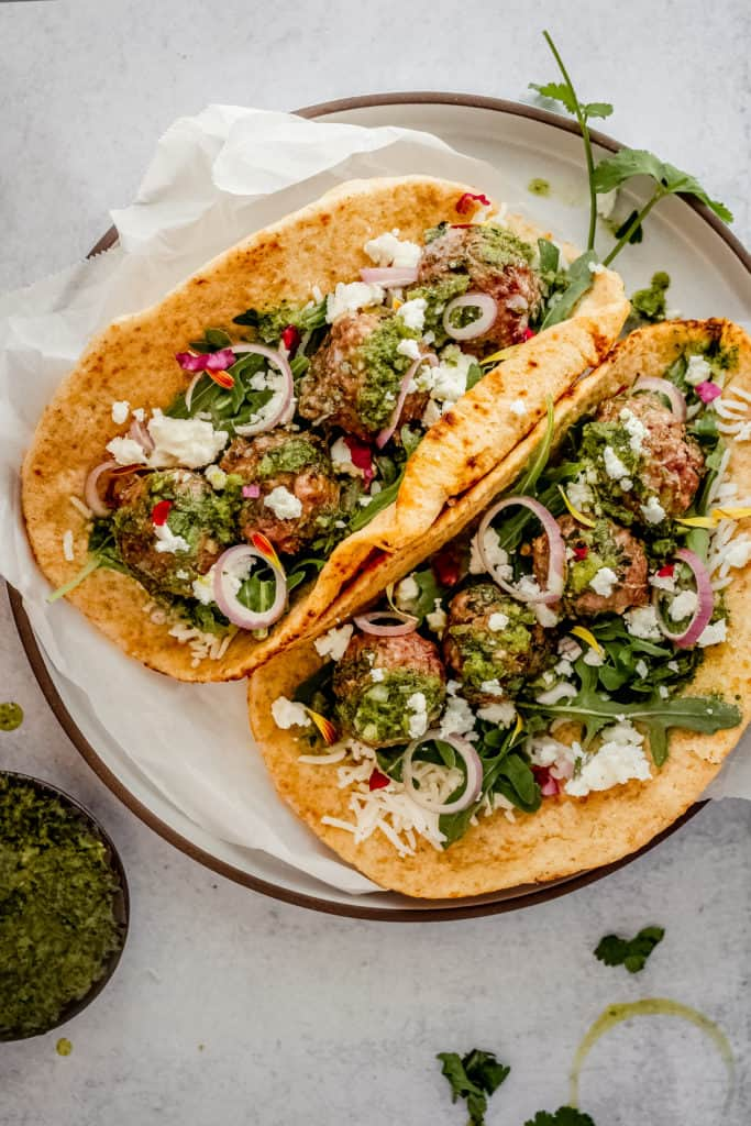 two pita wrap stuffed with rice, greens, chimichurri and lamb meatballs on a plate