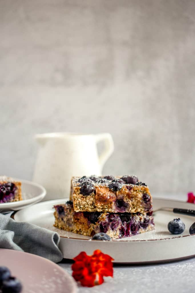 two slices of blueberry breakfast bars with cashew butter oozing out of the sides