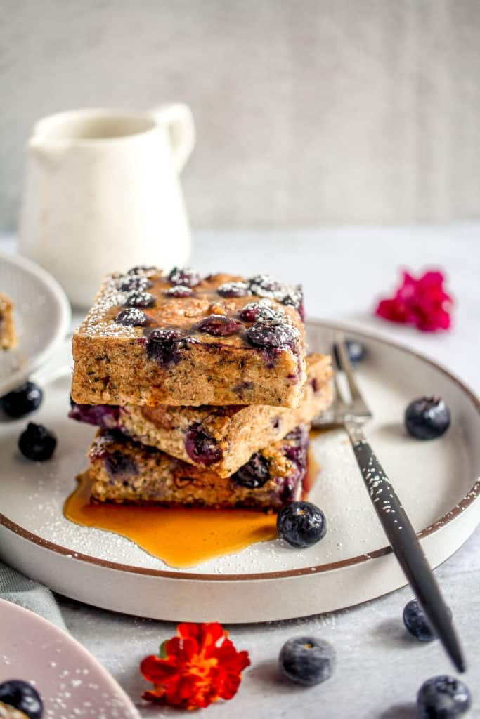 three slices of blueberry breakfast bars stacked with powdered sugar and maple syrup