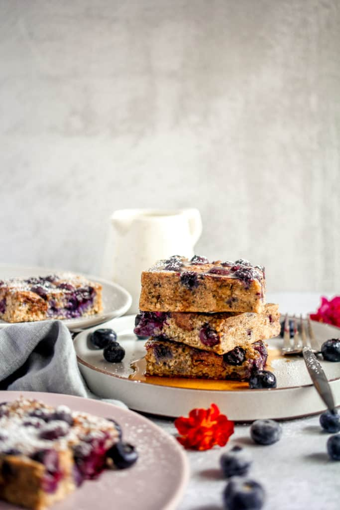 three slices of blueberry breakfast bars stacked with powdered sugar