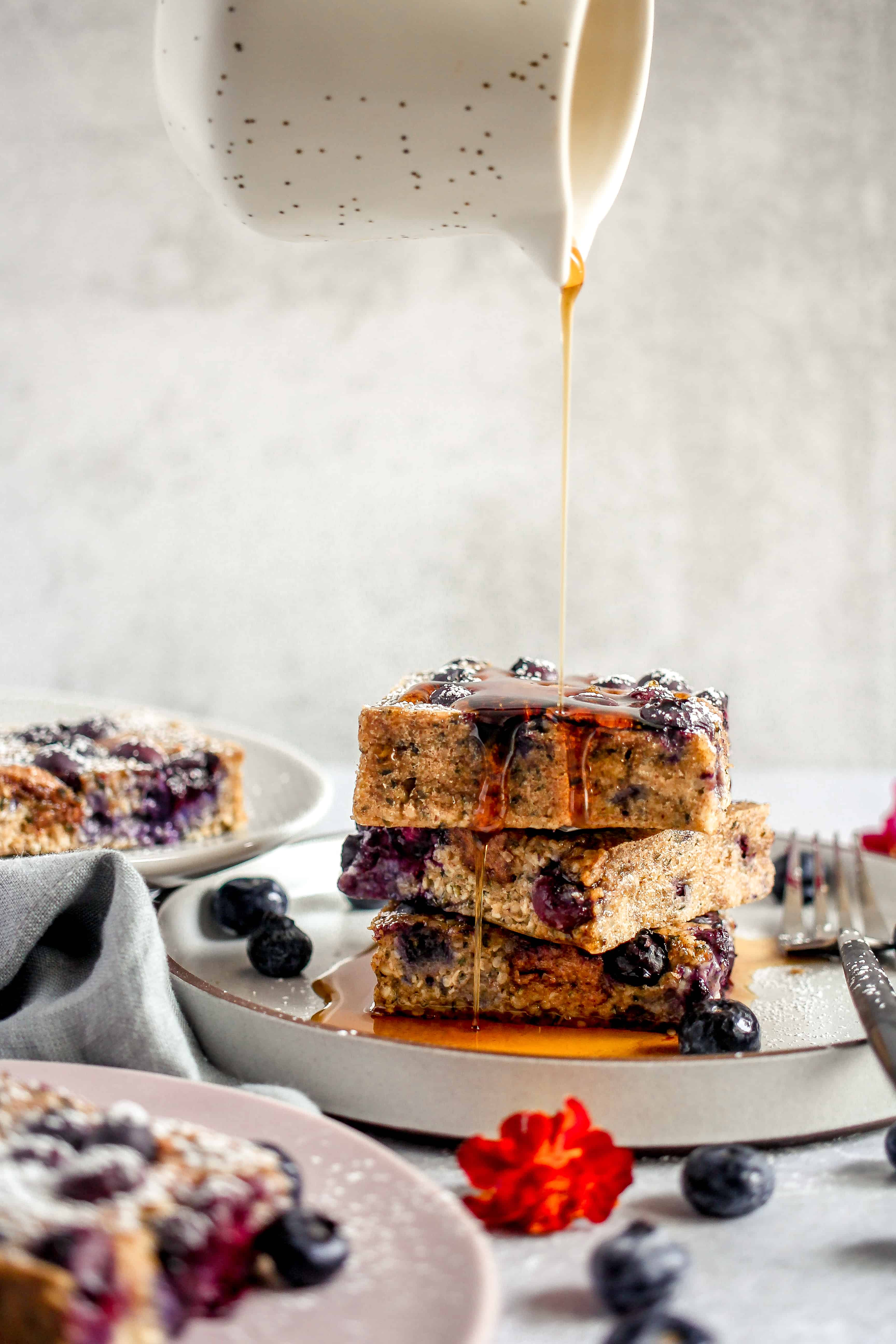 three slices of blueberry breakfast bars stacked with maple syrup being poured on