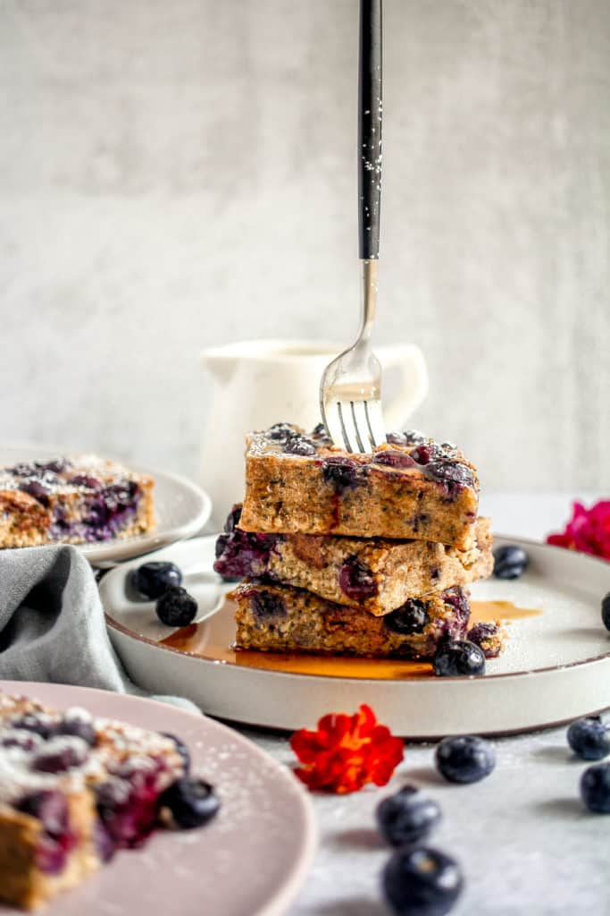 three slices of blueberry breakfast bars stacked with a fork stuck into the middle of the stack