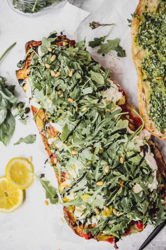 open face sandwich with roasted vegetables, burrata, arugula and pine nuts with pesto