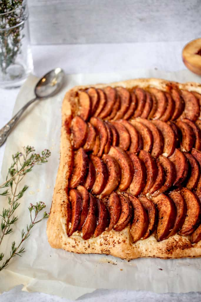 a tar with sliced peaches, roasted with honey and black pepper on parchment paper