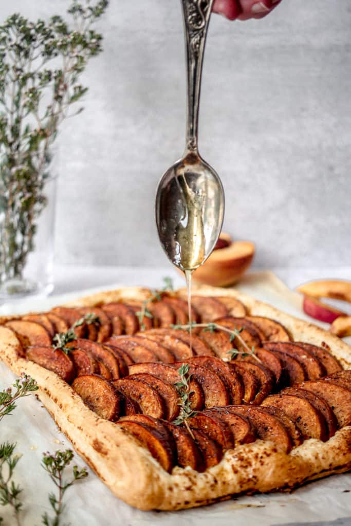 tart with sliced peaches being drizzled with honey