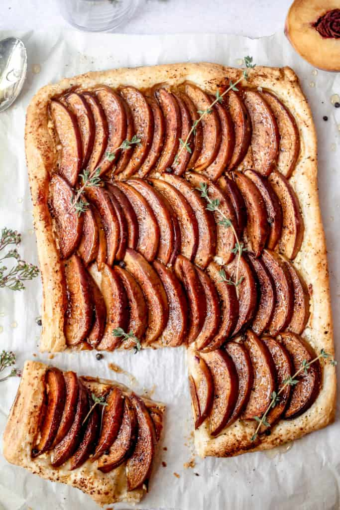 tart with sliced peaches and one slice cut and herbs on top