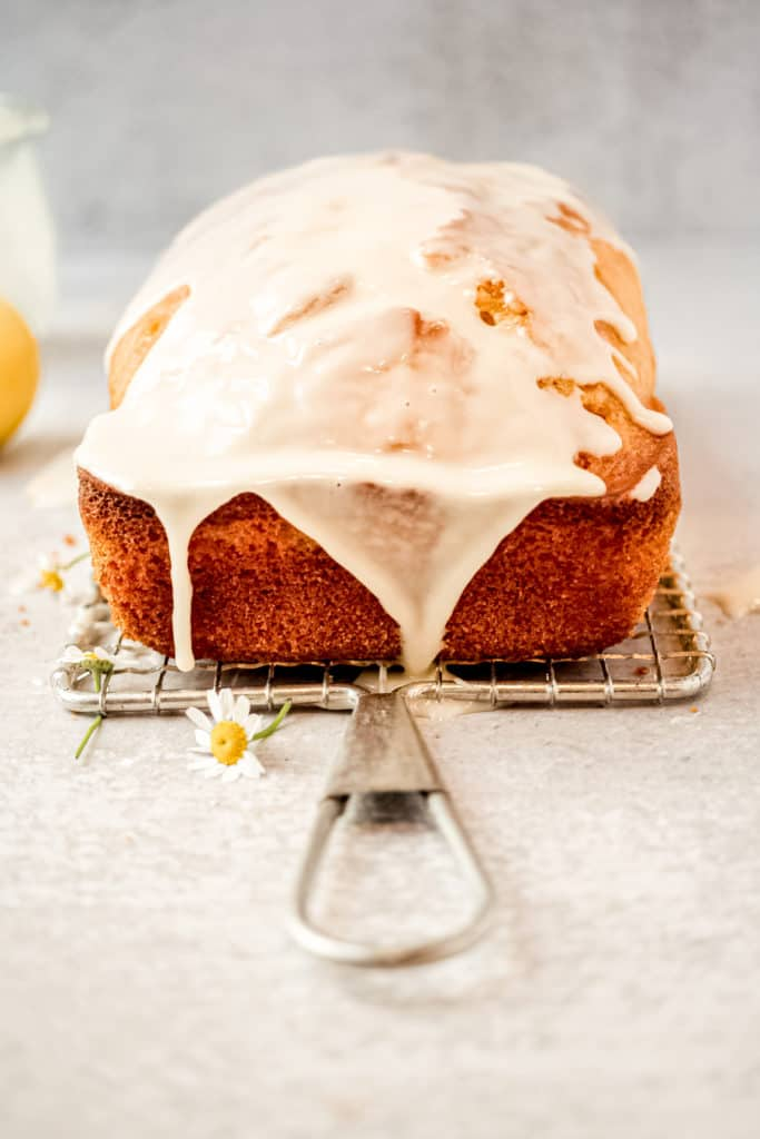 A loaf of lemon pound cake with lemon icing on a metal cake serve