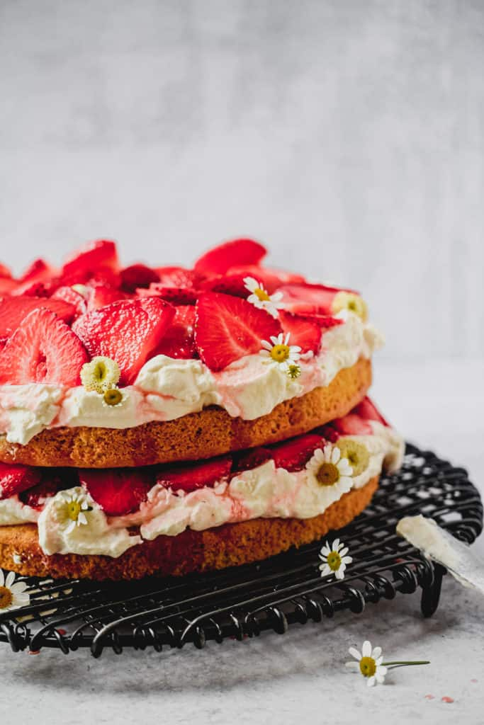 Almond flour cake with strawberries and coconut whipped cream on black cake stand with flowers