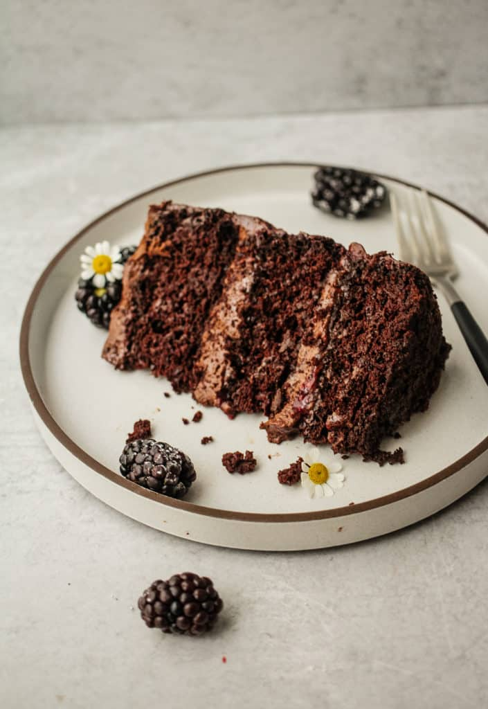 A thick slice of chocolate blackberry cake on a plate with blackberries