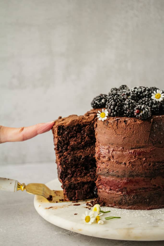 A slice of chocolate blackberry cake being removed to serve