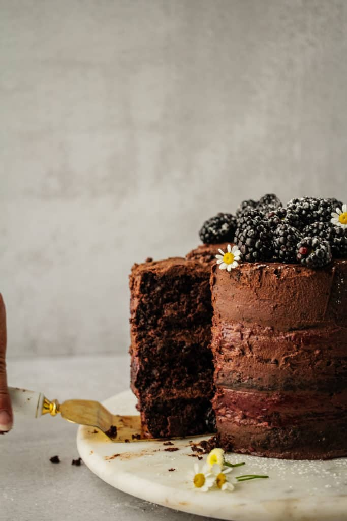 A slice of chocolate blackberry cake being lifted off of cake plate to serve