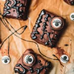 Three decorated brownies with spooky candy eyes and black icing