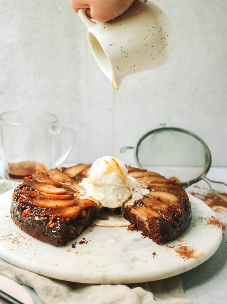 open shot of pear cake with scopp of melting ice cream