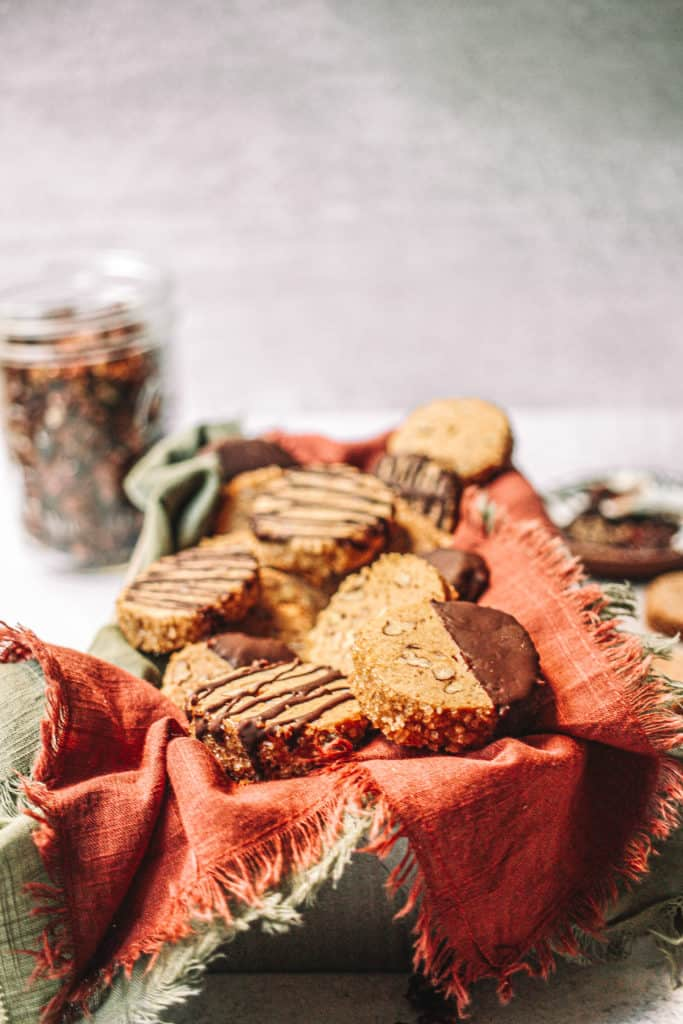 cookies in tin with pink napkin and jar of pecans in back