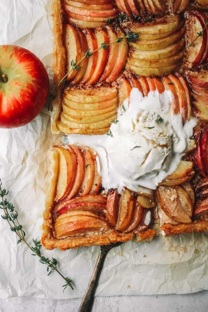 apple tart slice with whole apple on parchment paper