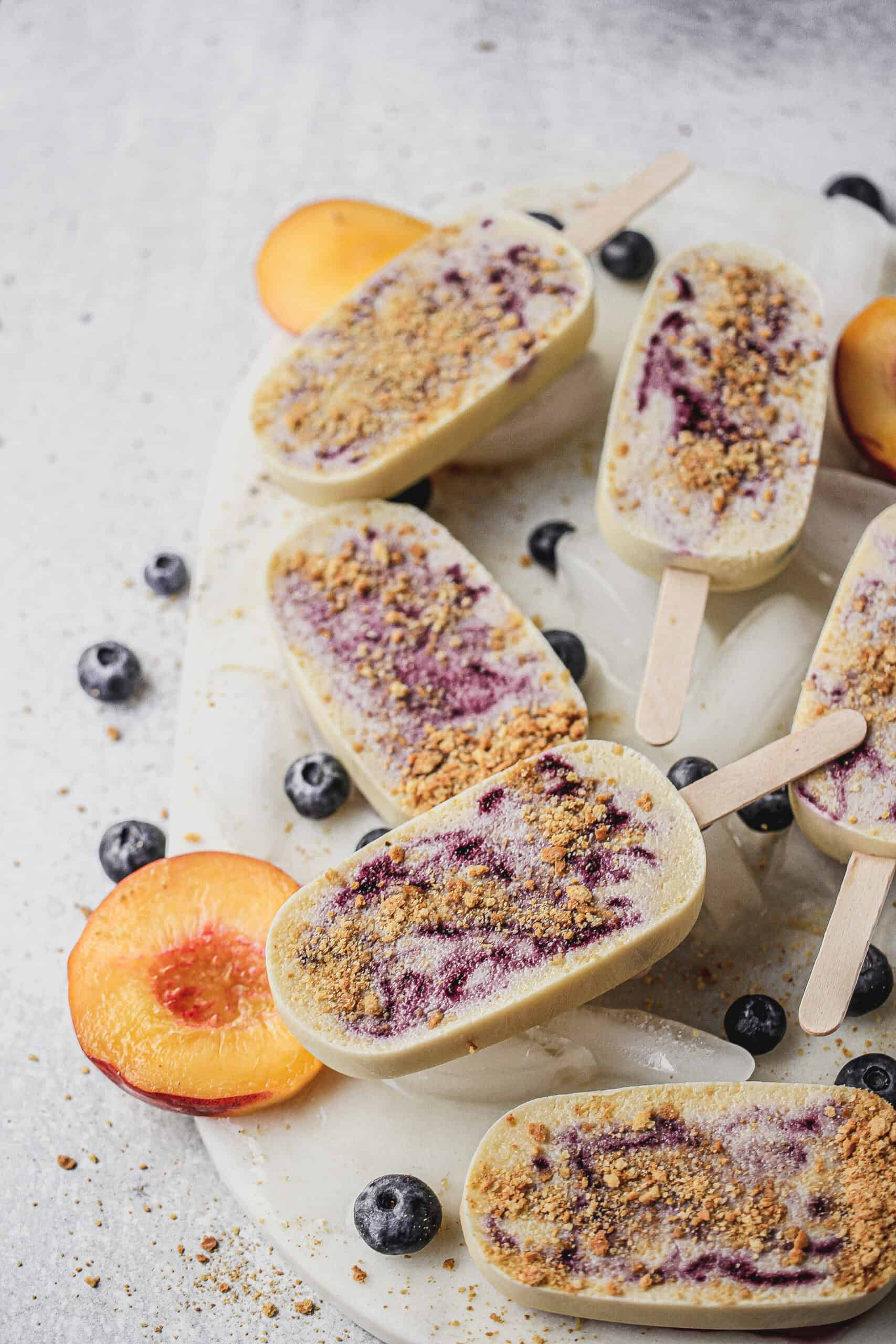 blueberry popsicles laying overtop ice on a marble platter with fresh peaches and blueberries