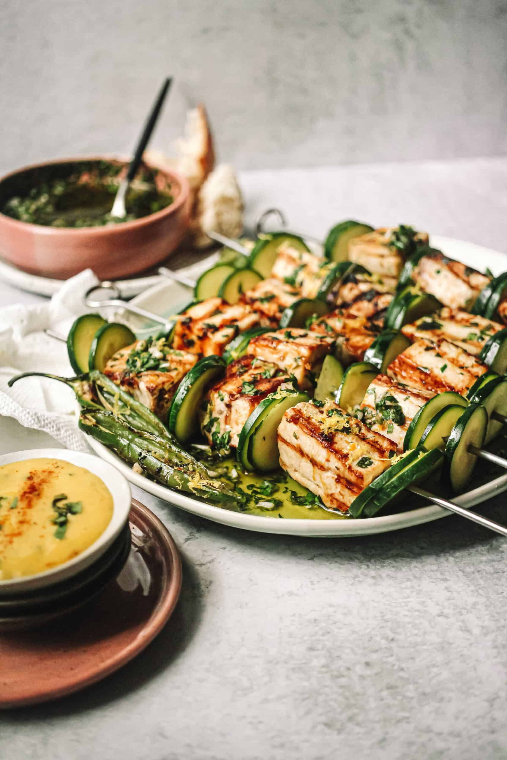 swordfish and zucchini on skewers on blue and white plate