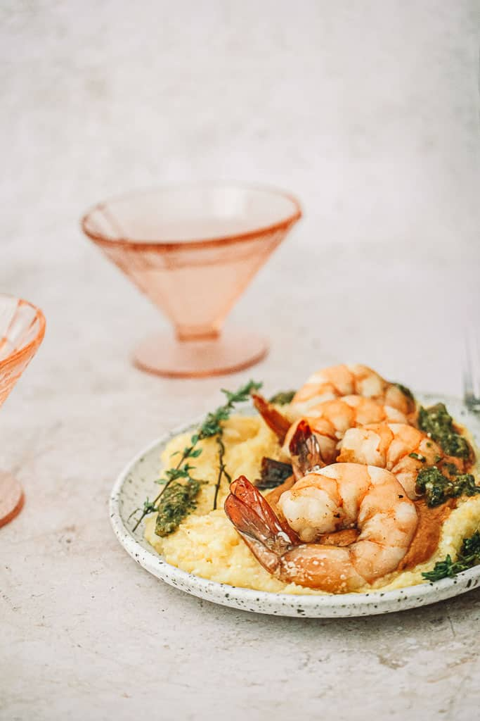 four cooked shrimp on top of a bed of polenta