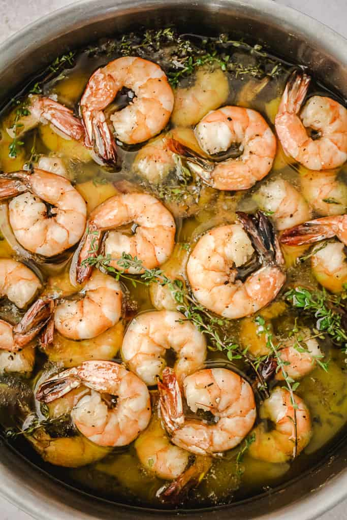 Many shrimp sitting in olive oil and fresh thyme in a pan