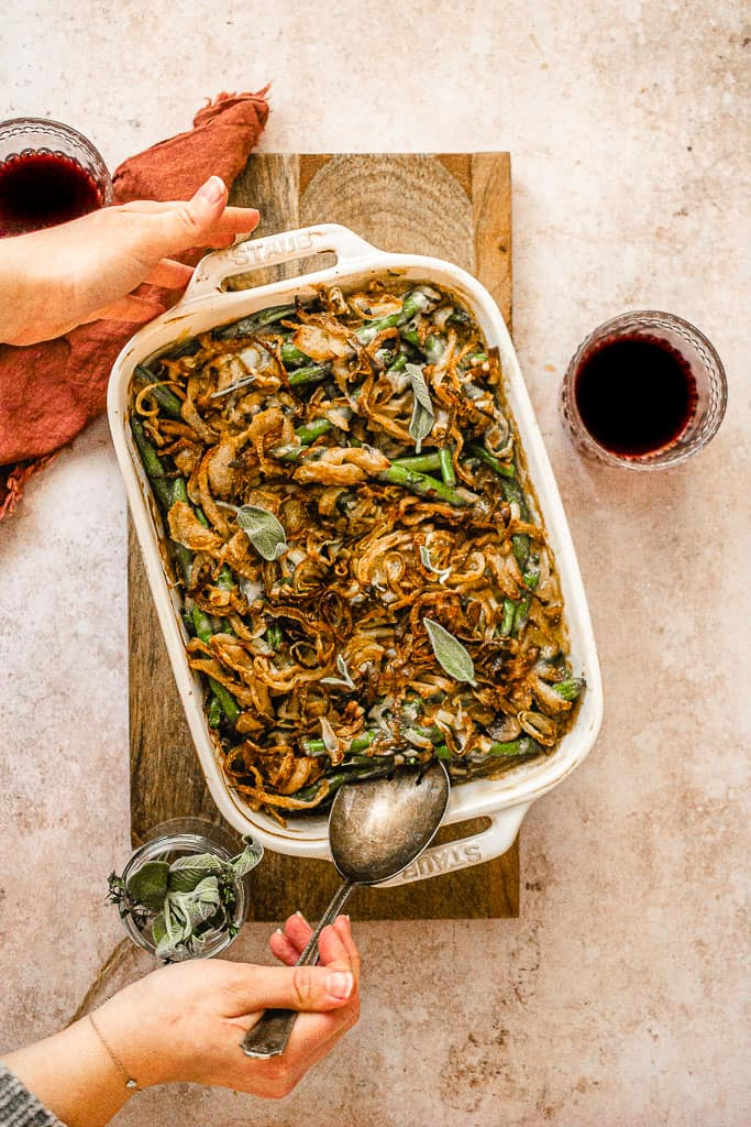 Hands scooping green bean casserole out of baking dish with large spoon.