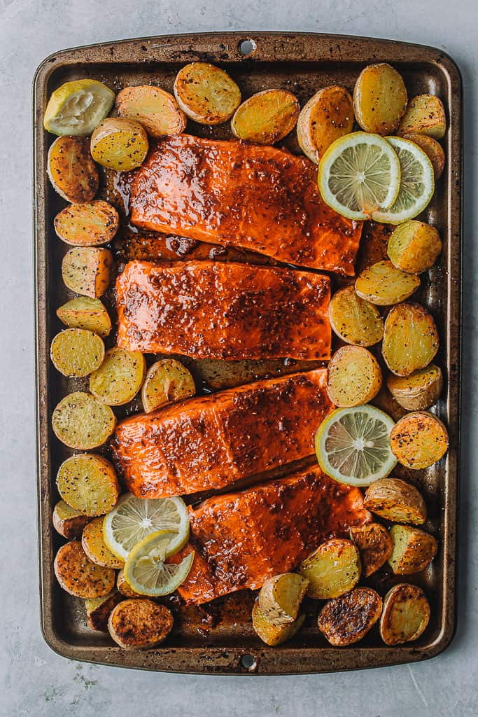 pre-baked salmon coated on sheet pan with potatoes and lemons.
