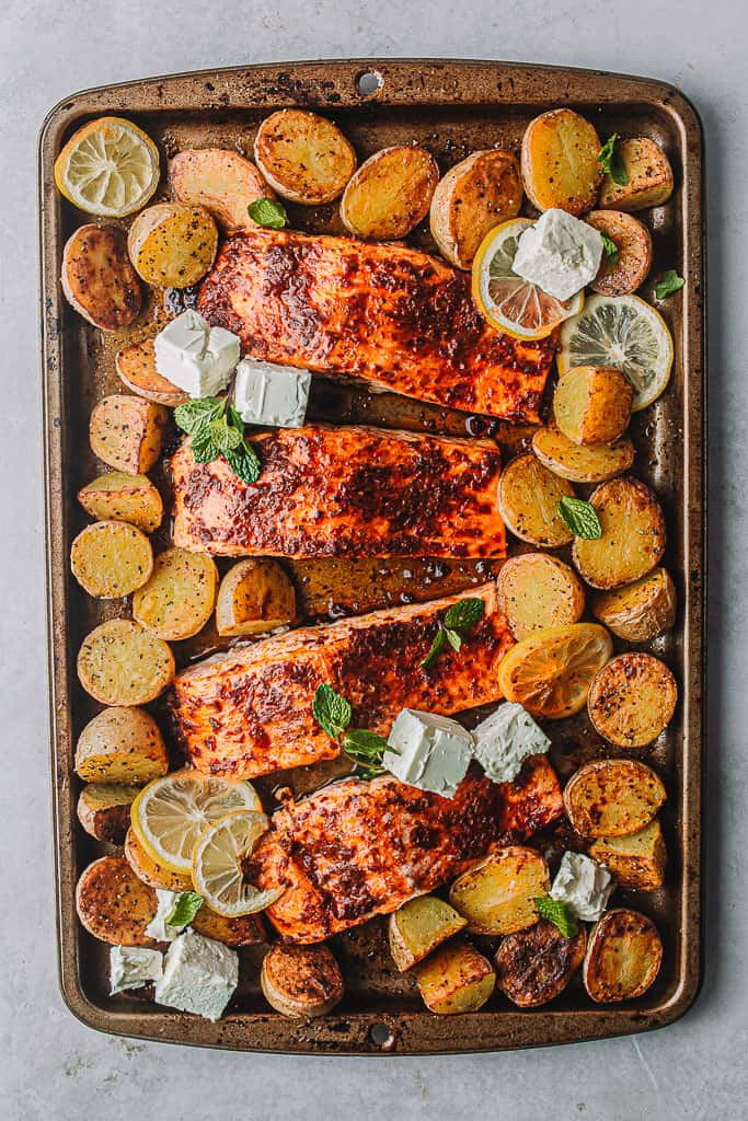 cooked harissa salmon on a sheet pan with potatoes and feta cheese.