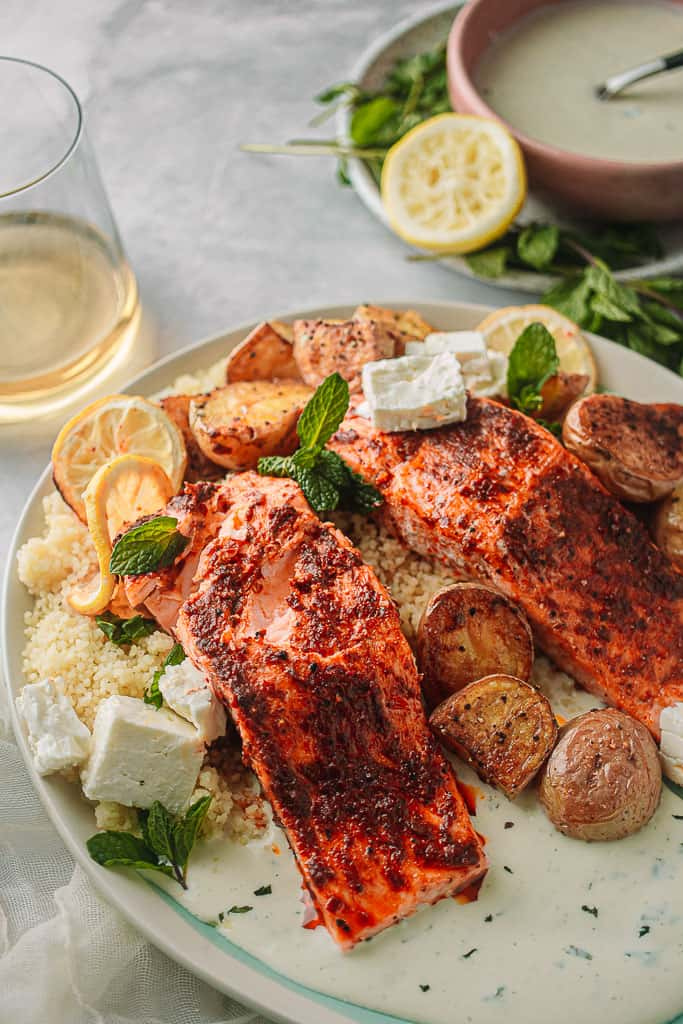 plate with 2 salmon filets over couscous with a white sauce and potatoes.