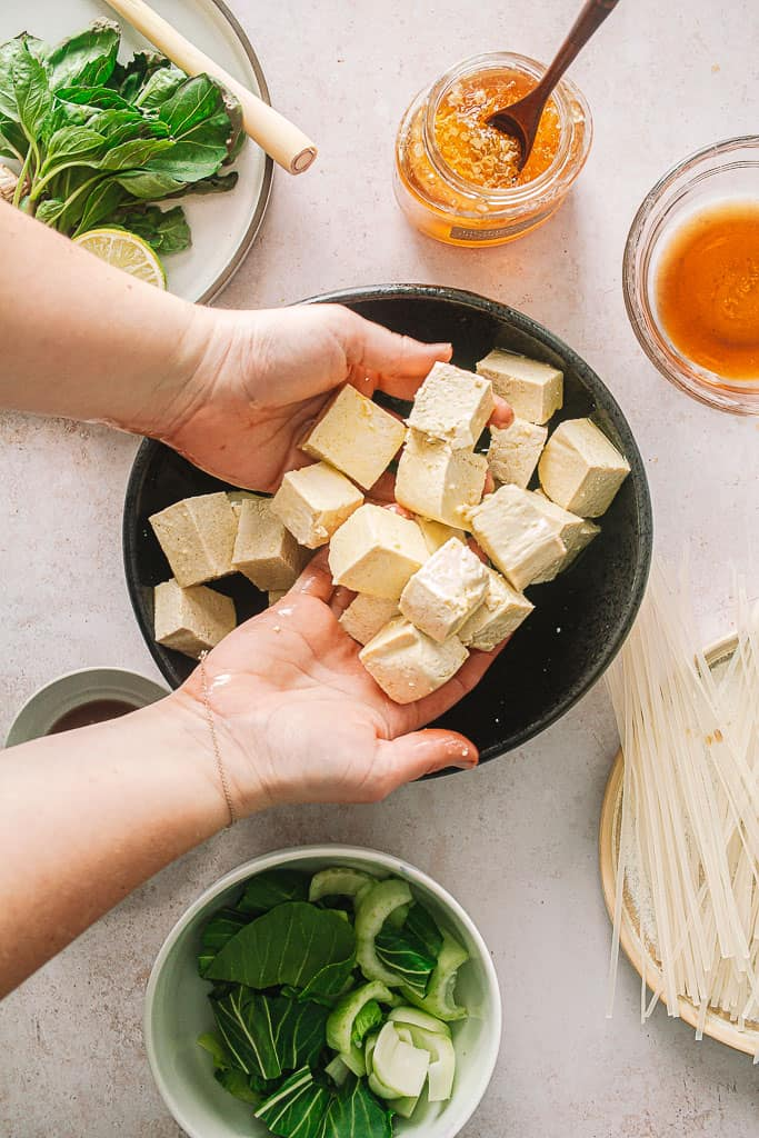 hands tossing cubed tofu in olive oil