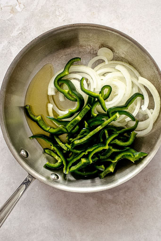 Olive oil, sliced poblano peppers, and sliced onions in a stainless steel pan.