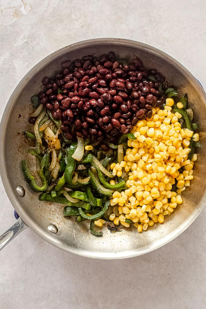 Poblano and onion slices with black beans and yellow corn in a stainless steel pan.