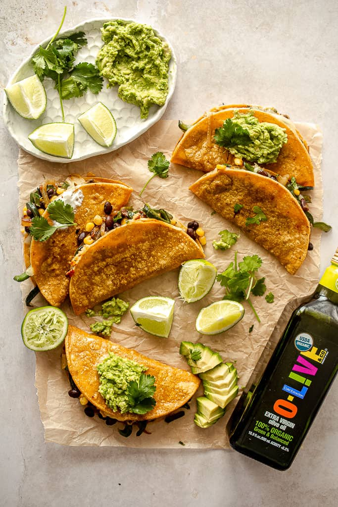 Five black bean quesadillas on parchment paper with guacamole, limes, and a bottle of olive oil.