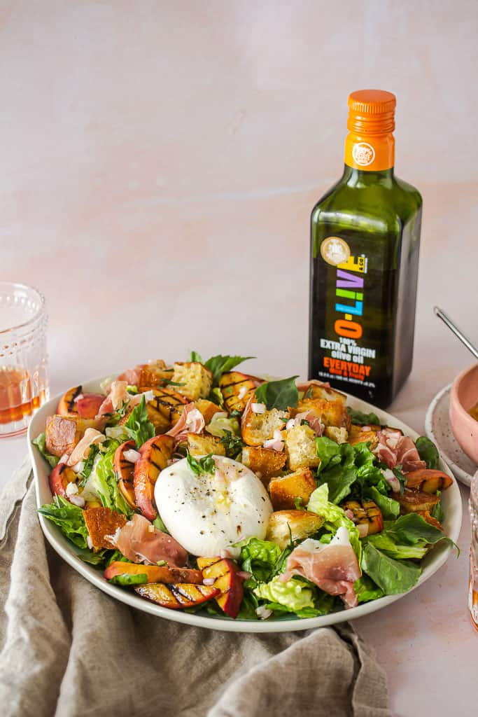 panzanella salad on a plate next to a bottle of olive oil.