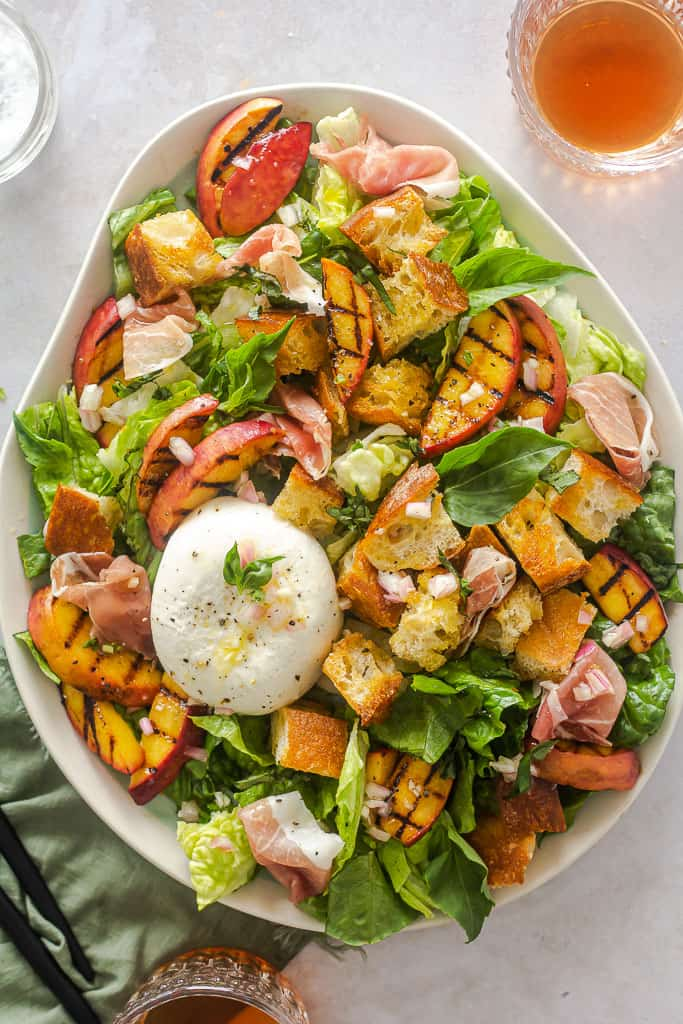 Peach salad with bread, cheese, and prosciutto on a plate surrounded by 2 drinks.