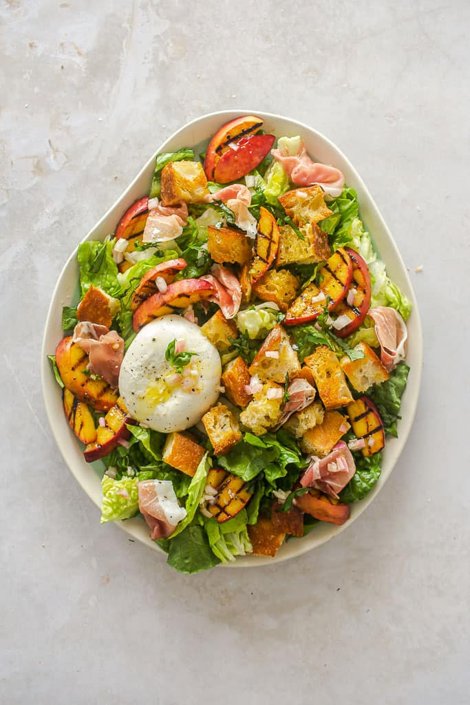 Salad plated up with greens, grilled peaches, buratta cheese, and croutons.